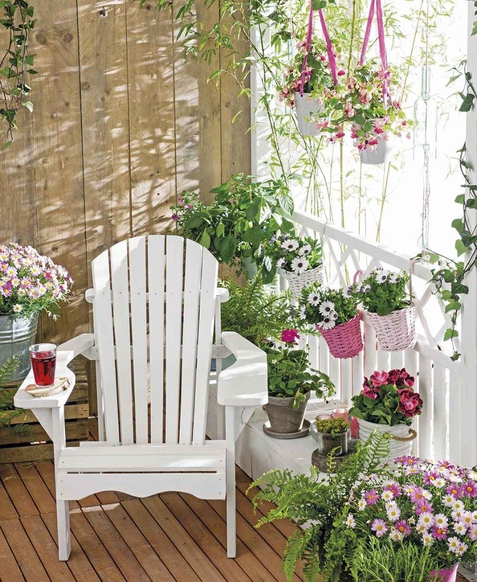 Een kleine buitenruimte met bloemen en planten op verschillende hoogtes