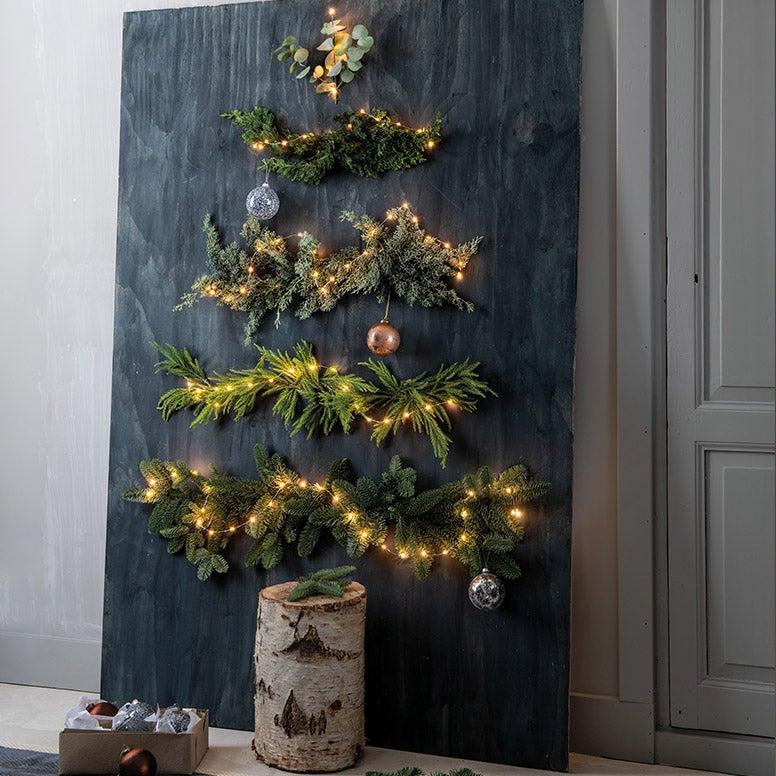 Alternatieve kerstboom van takken aan de muur