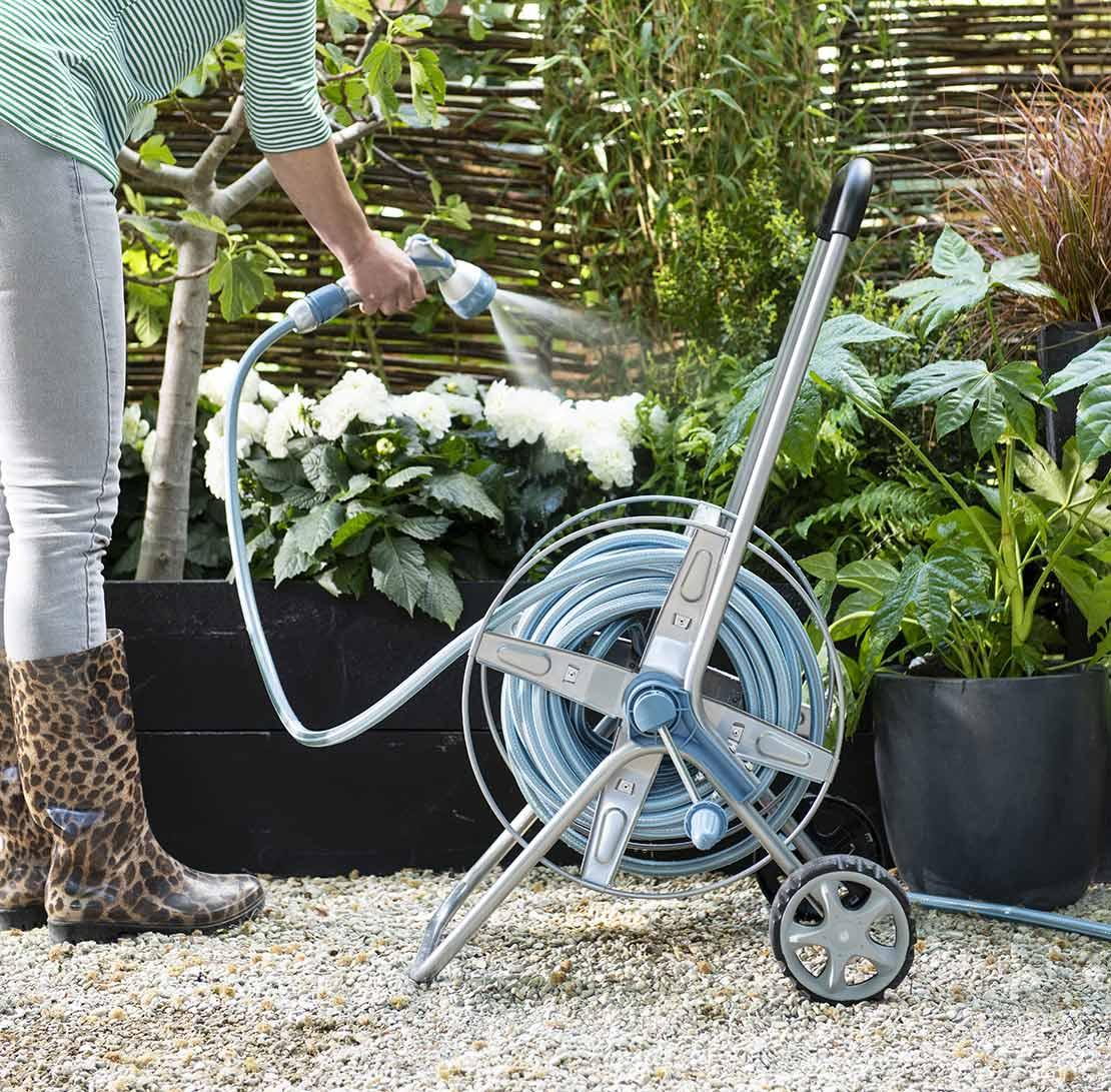 Tuin water geven met tuinslang en slangenwagen